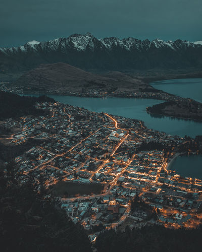 High angle view of illuminated cityscape by lake against mountains at night