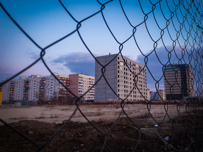 View of city seen through chainlink fence