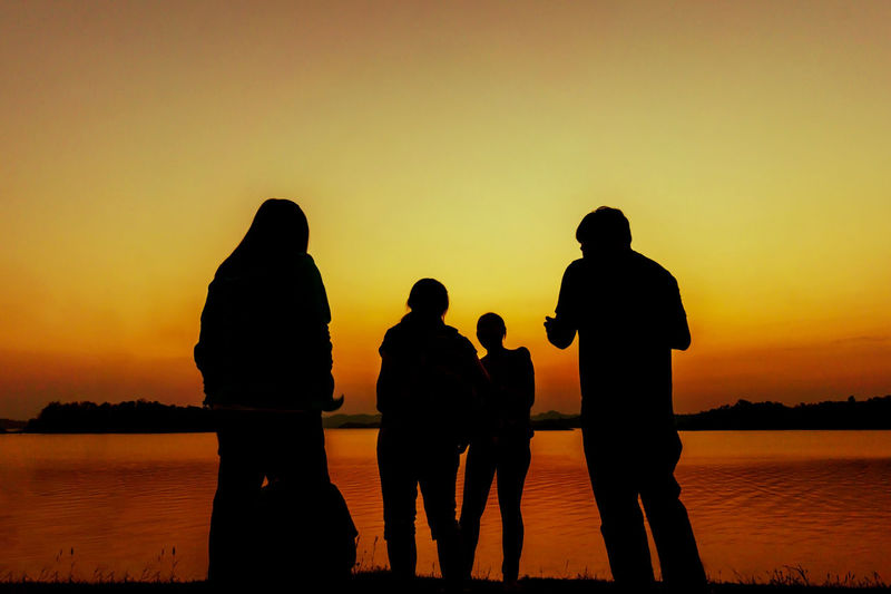 Silhouette people looking at lake against orange sky
