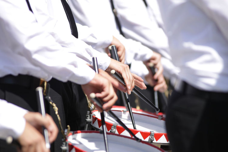 Midsection of musicians playing drum