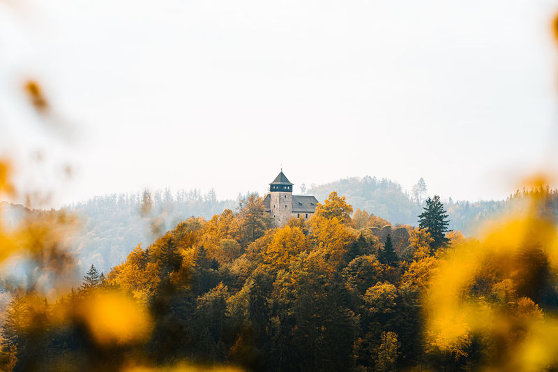 Scenic view of trees and buildings against sky during autumn