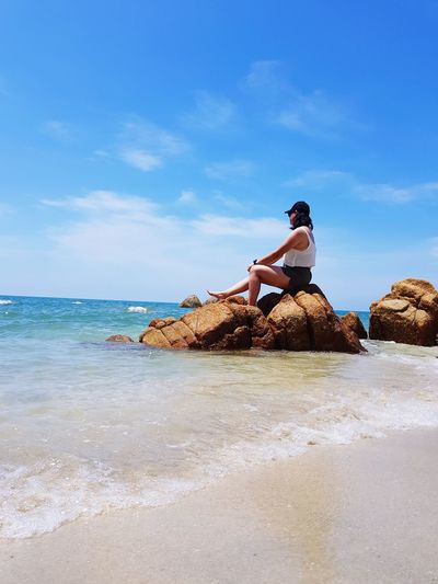 Side view of woman sitting on rock at beach against sky