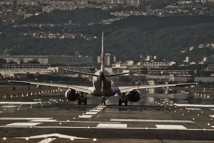 Airplane at airport runway in city