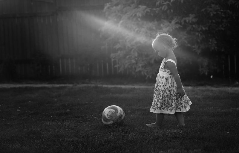 Side view of girl playing with soccer ball in lawn