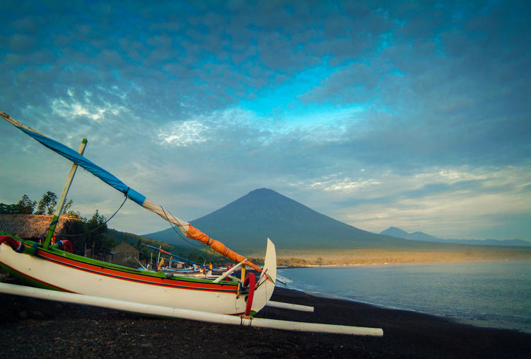 Mt. Agung, Bali. Gunung Agung has recently experienced frequent volcanic earthquakes that indicates volcanic activity instability. The volcano last erupted in 1963 and killed over 1100 people. The Jemeluk area of Amed, a sleepy fishing village, lies right at the foot of the mountain. ASIA Bali INDONESIA MT Travel Agung Balinese Beach Boat Cloud - Sky Fishing Boat Gunung Jukung Mountain Nature Nautical Vessel No People Outdoors Outrigger Sea Sky Transportation Volcanic  Volcano Water