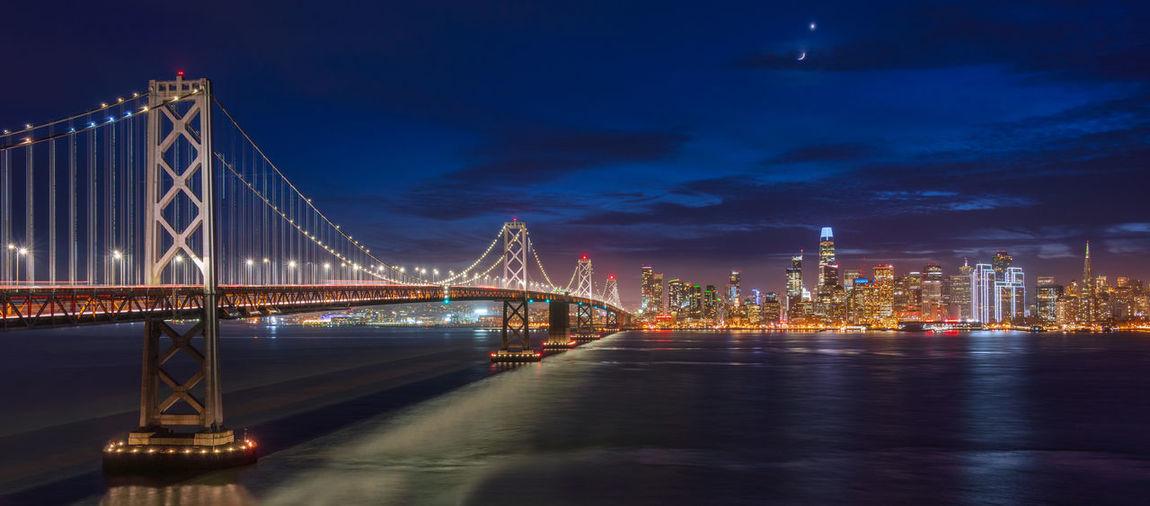 Illuminated bay bridge at night and the san francisco skyline