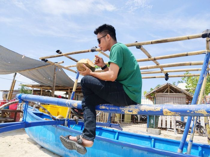 Low angle view of man drinking coconut water while sitting on nautical vessel against sky