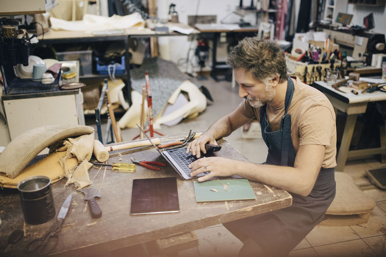 Male craftsperson using laptop at workbench in workshop