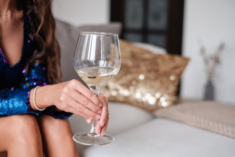 Female hand holding glass with white wine One Person Glass Celebration Event Celebration Holding Lifestyles Food And Drink Focus On Foreground Refreshment Wine Wineglass Party Household Equipment Alcohol Women Drink Leisure Activity Drinking Glass Hairstyle Sitting Party - Social Event Shine Bright Like A Diamond  Shine Well Dressed