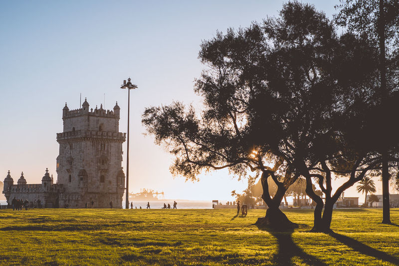 Belem Tower from the distance. Architecture Built Structure Travel Destinations Lisbon Portugal Europe Plant Tree Sky Building Exterior Grass Nature Field The Past History Tower Religion Building Outdoors Spirituality Growth Day Park