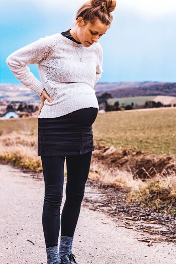 Full length of pregnant woman standing on mountain against sky