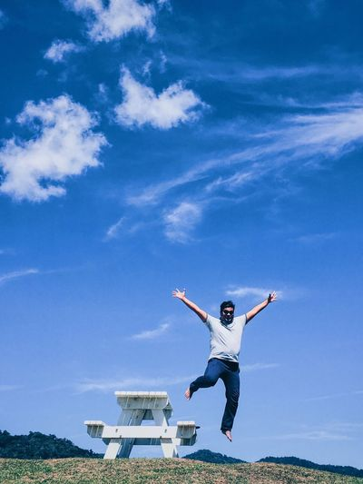 Low angle view of man with arms raised jumping from picnic table against blue sky
