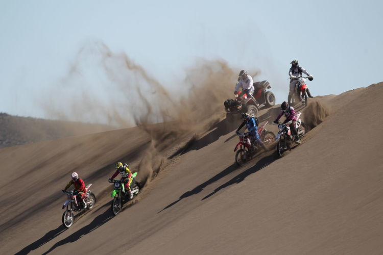 People motocross riding in desert