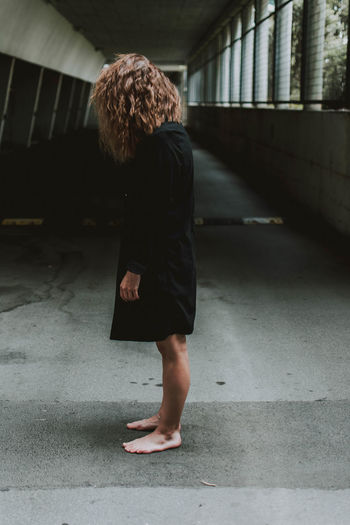 Side view full length of woman standing in covered walkway