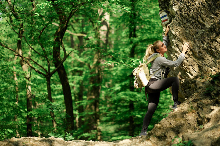 Young Woman With Backpack Climbing Tree In Forest