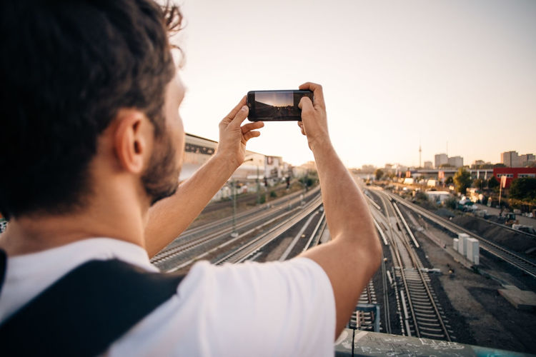Rear view of man photographing using smart phone against sky