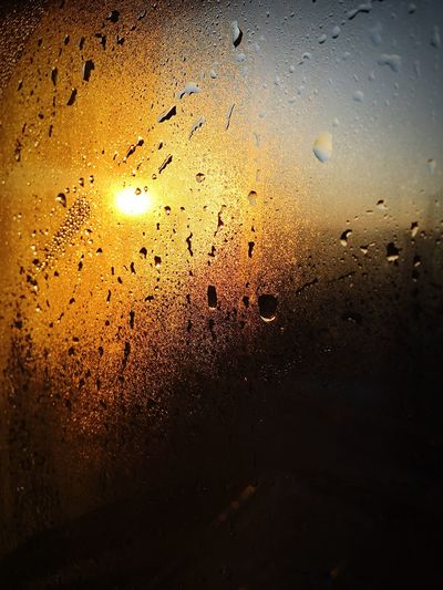 Close-up of wet glass against sky during sunset