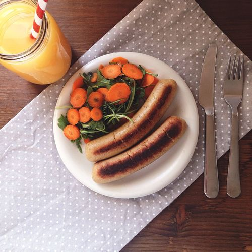 Meal Of Sausages, Carrot And Arugula Salad, With Orange Juice