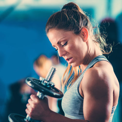 Side view of woman lifting dumbbell in gym