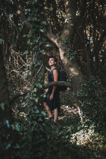 Portrait of young woman standing by tree trunk in forest