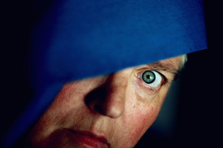 Portrait Of Woman Wearing Blue Hood Against Black Background
