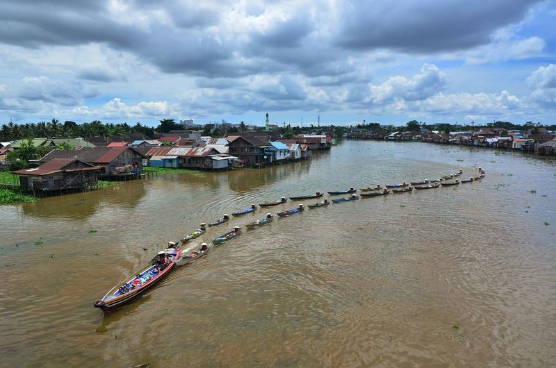 High angle view of boats in river by buildings against sky
