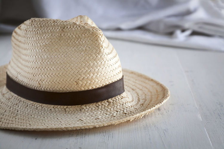 Close-up Clothing Day Fashion Focus On Foreground Hat Headwear Indoors  No People Personal Accessory Place Mat Protection Safety Security Still Life Straw Hat Sun Hat Table Textile Wood - Material