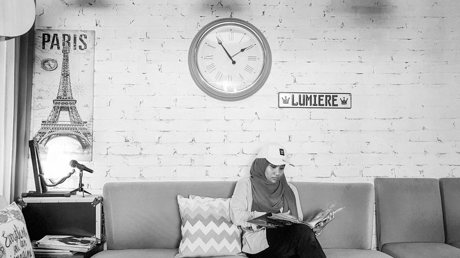 Woman sitting on sofa against wall