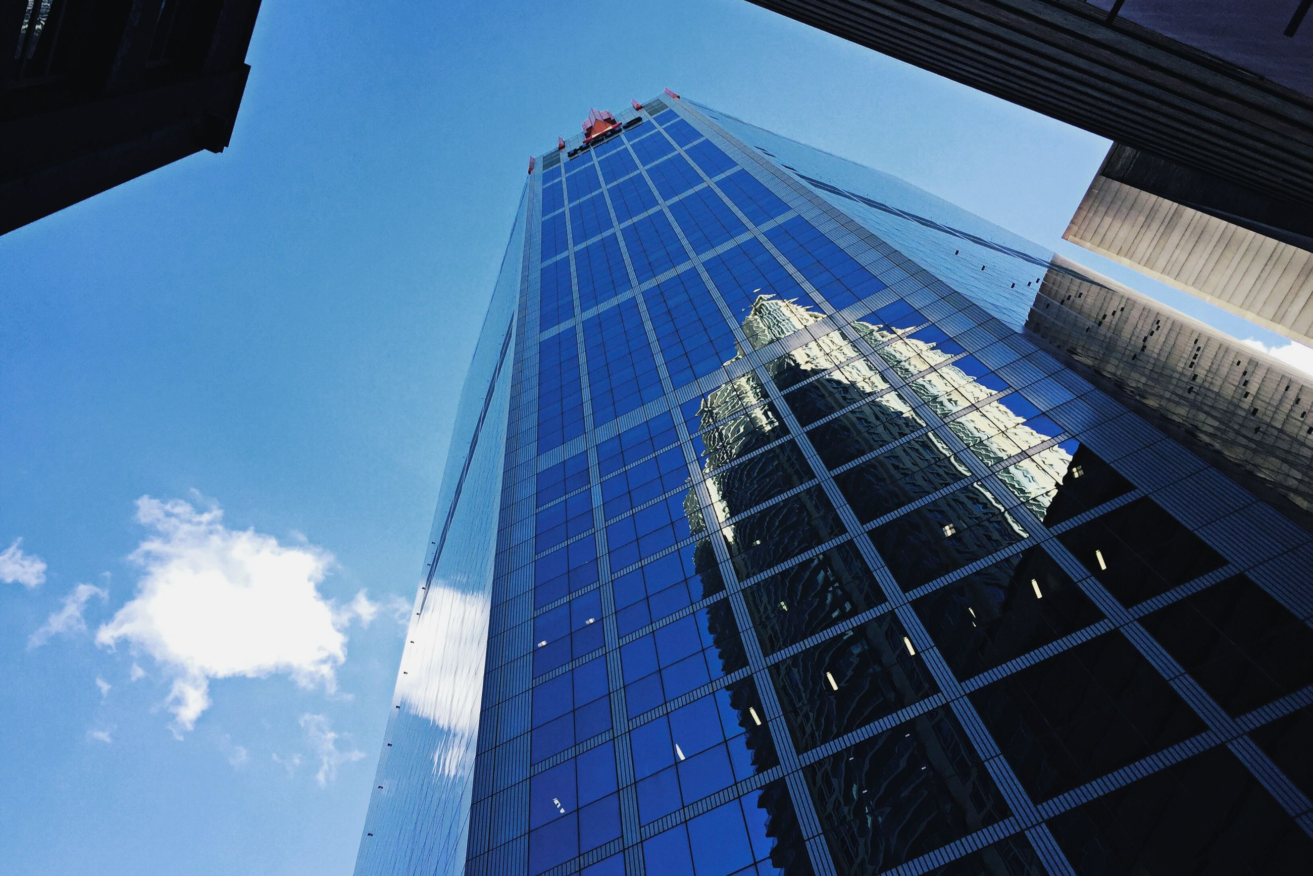 architecture, built structure, low angle view, building exterior, modern, skyscraper, tall - high, office building, city, glass - material, tower, reflection, capital cities, building, sky, development, day, city life, travel destinations, outdoors