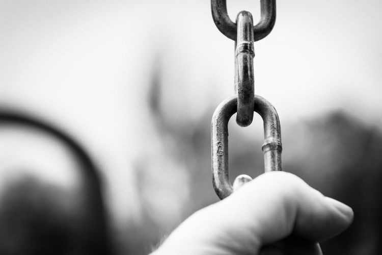 Close-up of hand holding chain