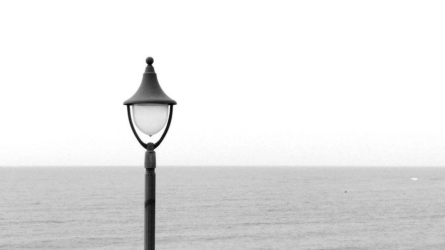 Street light on beach against clear sky