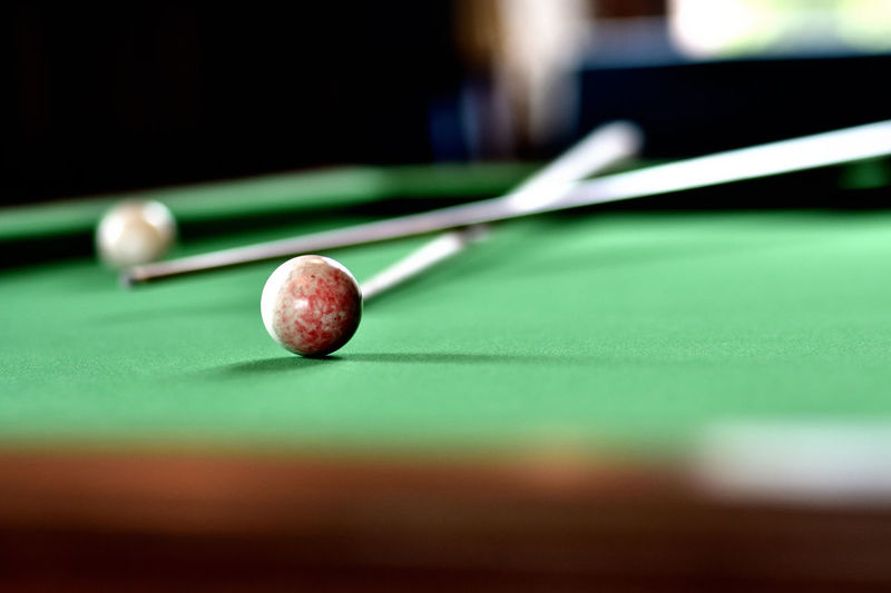 Close-up of pool balls by cue on table