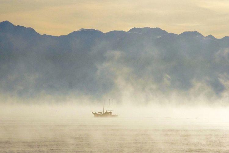 Sailboat amidst mist on sea against sky