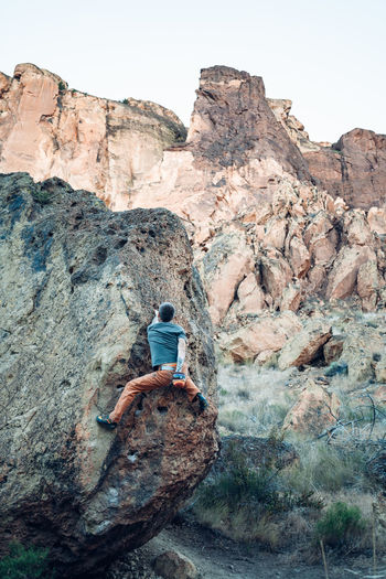 Rear view of person on rock by rocky mountains against sky