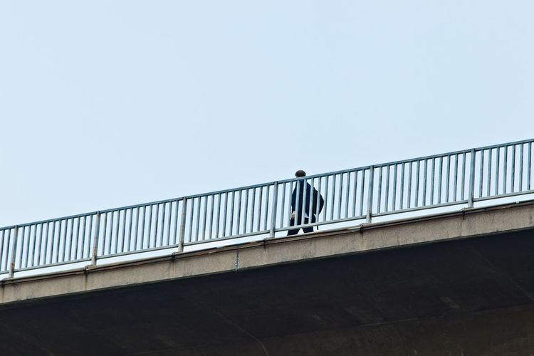Low angle view of man standing on railing against sky