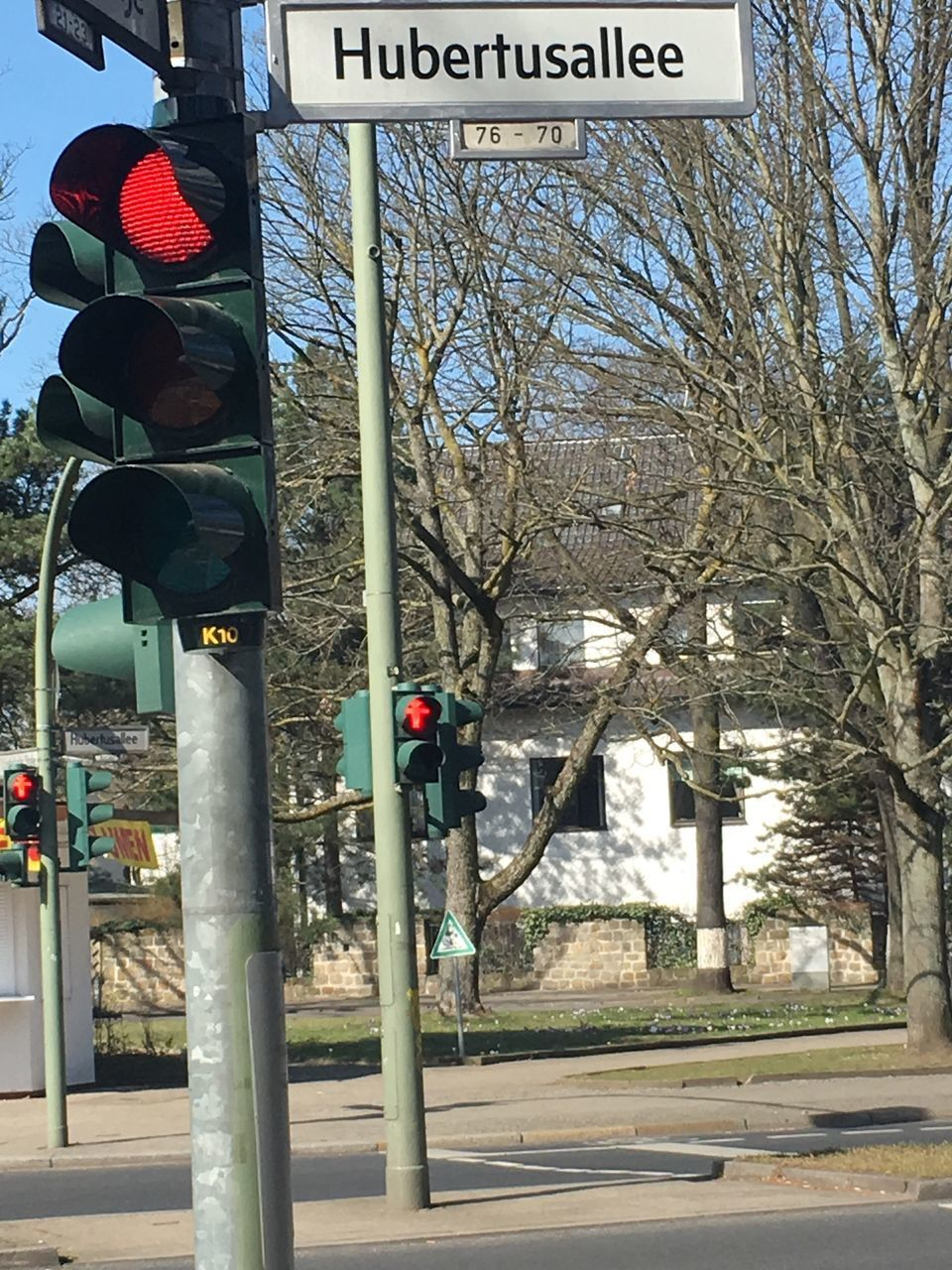 communication, road sign, text, guidance, stoplight, red light, traffic light, traffic signal, day, outdoors, tree, bare tree, street name sign, building exterior, road, no people, signal, architecture, city