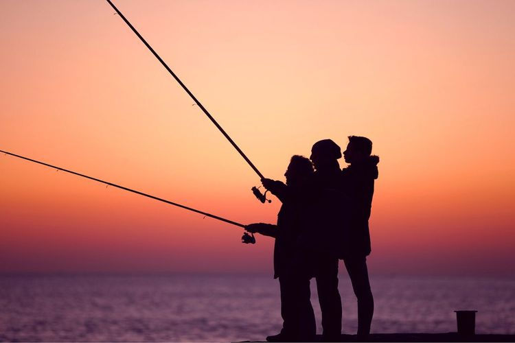 Silhouette friends fishing at beach against sky during sunset