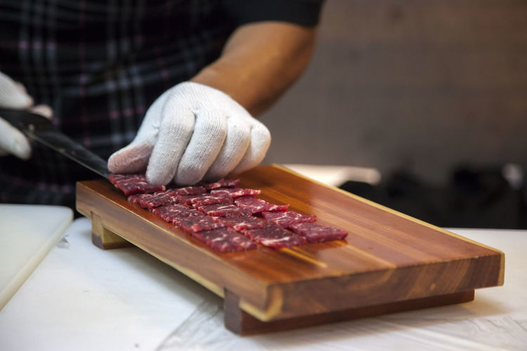 Midsection of man arranging meat on cutting board in kitchen