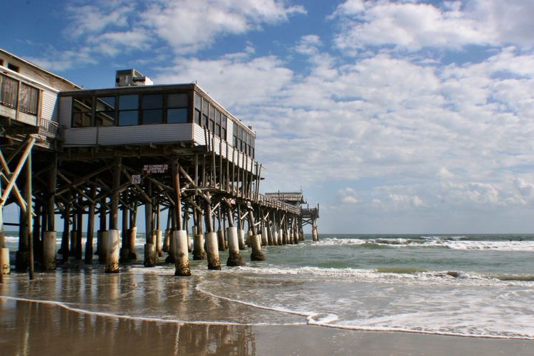 Low angle view of pier over beach against cloudy sky