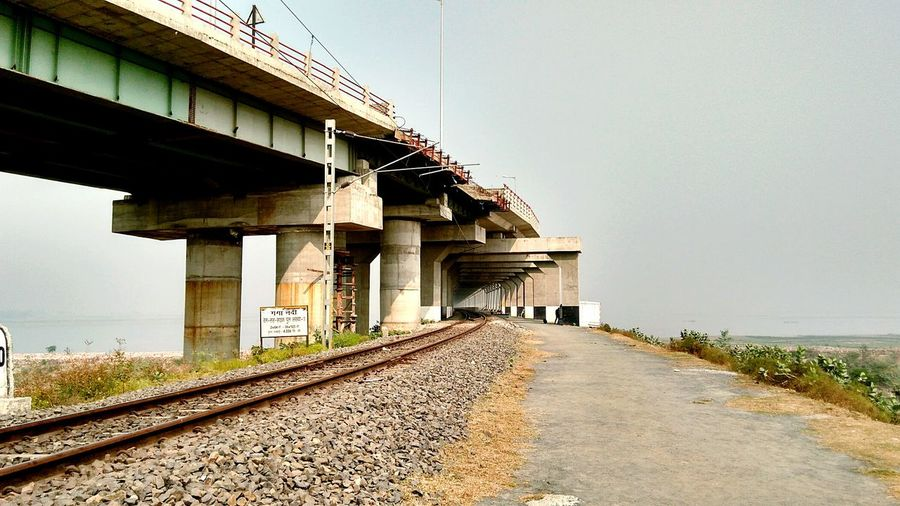 Railroad tracks by bridge against clear sky