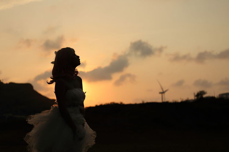 Silhouette of woman  in white dress standing on field