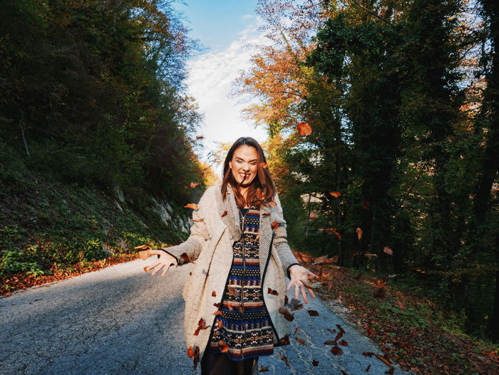 Portrait of smiling young woman on road amidst trees