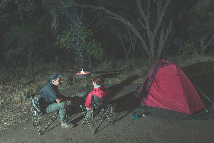 People Relaxing By Tent At Night