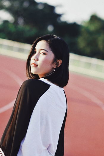 Portrait of young woman standing on running track
