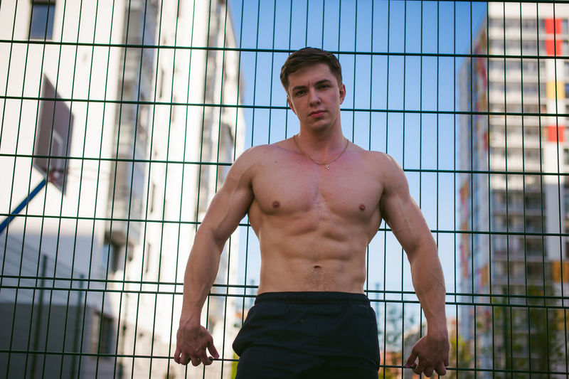 Portrait of muscular man standing against fence at park