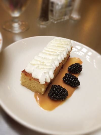 High Angle View Of Hazelnut Cake With Blackberries Served In Plate On Table