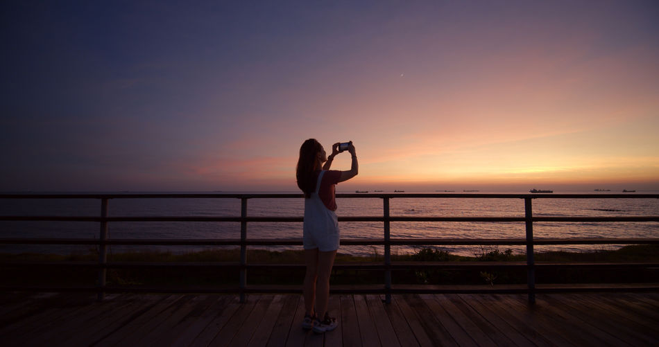 Mid adult woman taking photograph while standing by railing against sea during sunset