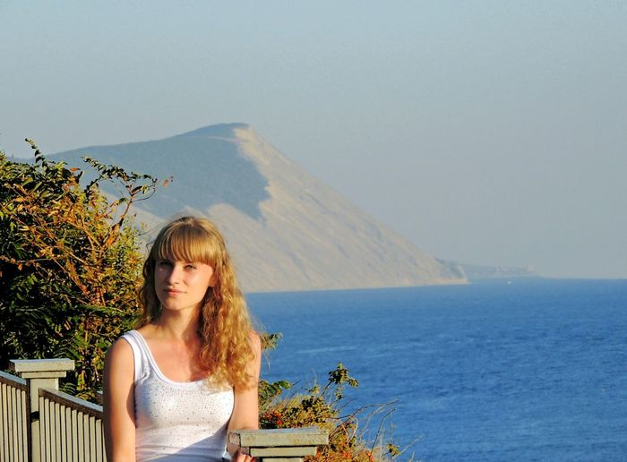 Portrait of woman standing on bridge by sea and mountain against clear sky