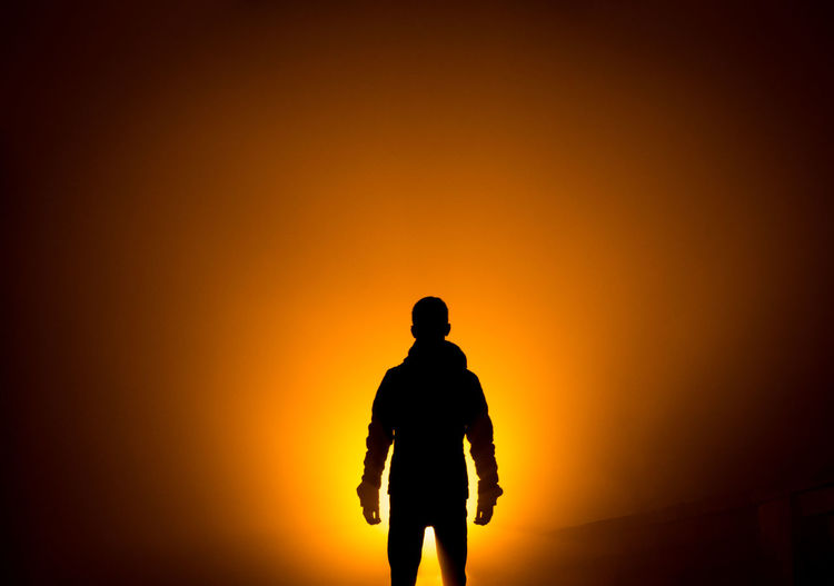 Silhouette man standing against orange sky