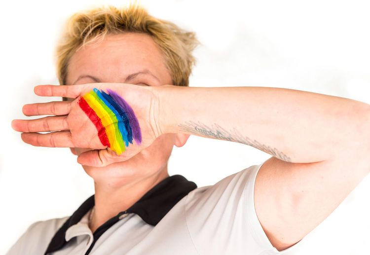 Person with rainbow flag paint on hand against white background